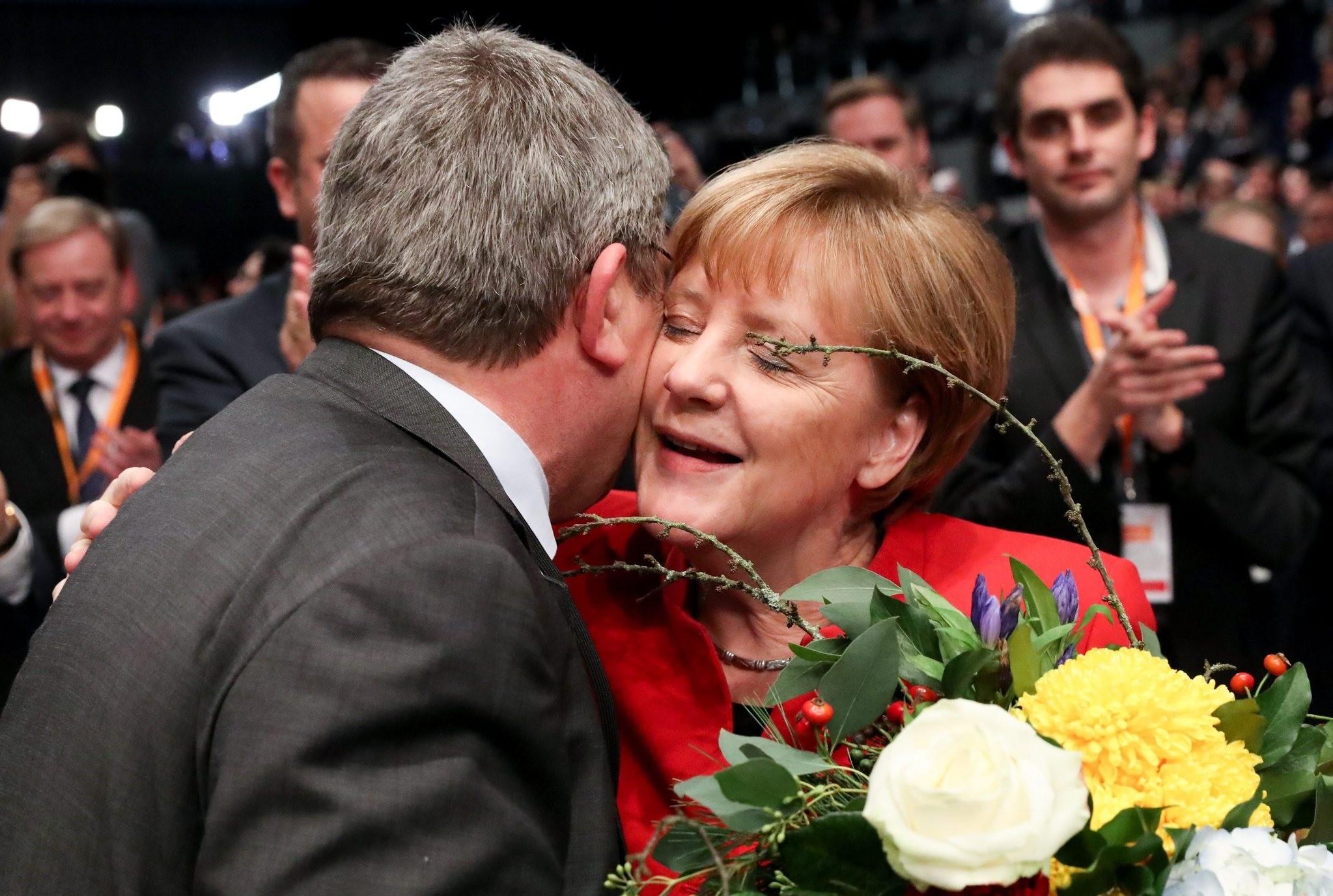 The Interior Minister of the German state of Mecklenburg-Western Pomerania Lorenz Caffier (L) congratulates German Chancellor Merkel. (AP Photo)