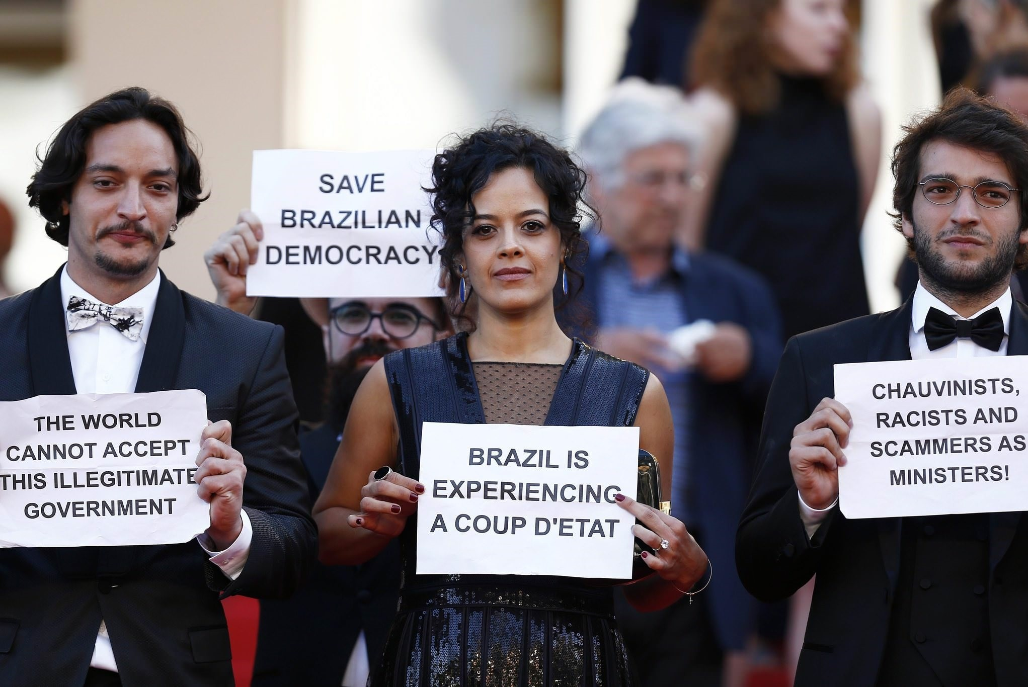 Brazilian actress Maeve Jinkings (C) holds a sign reading 'Brazil is experiencing a coup d'etat' as she leaves after the screening of 'Aquarius' during the 69th annual Cannes Film Festival, in Cannes, France, 17 May 2016. (EPA Photo)