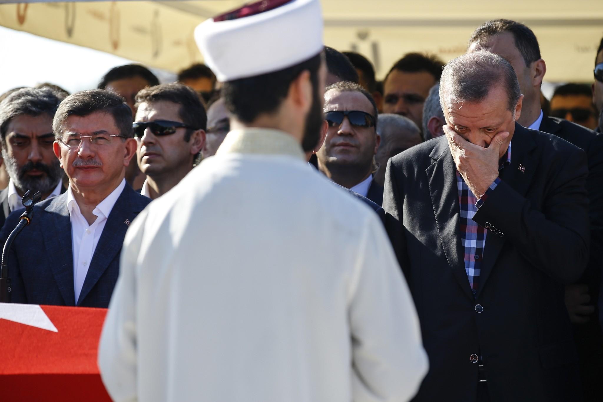 Turkish President Recep Tayyip Erdogan right, wipes his tears during the funeral of Mustafa Cambaz, Erol and Abdullah Olcak.