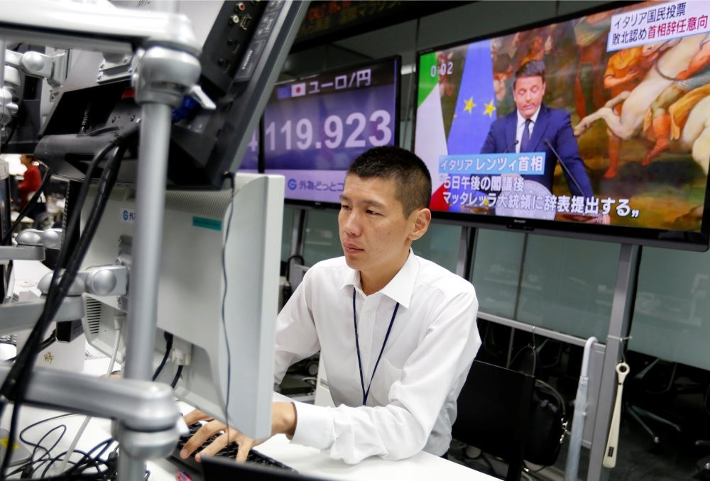 An employee of a foreign exchange trading company works in front of monitors showing Italian Prime Minister Matteo Renzi on TV news, and the Japanese yen's exchange rate against the euro in Tokyo, Japan.