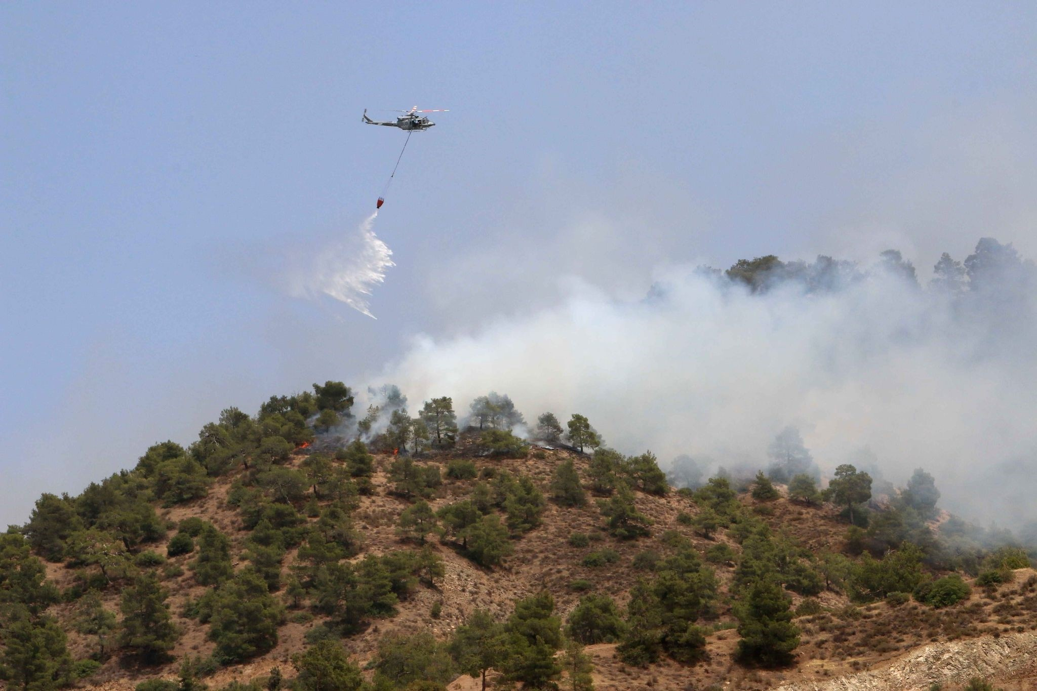 A helicopter drops water on a forest fire in the Cypriot village of Eyrixou in the Trodos mountain area on June 20, 2016. (AFP Photo)