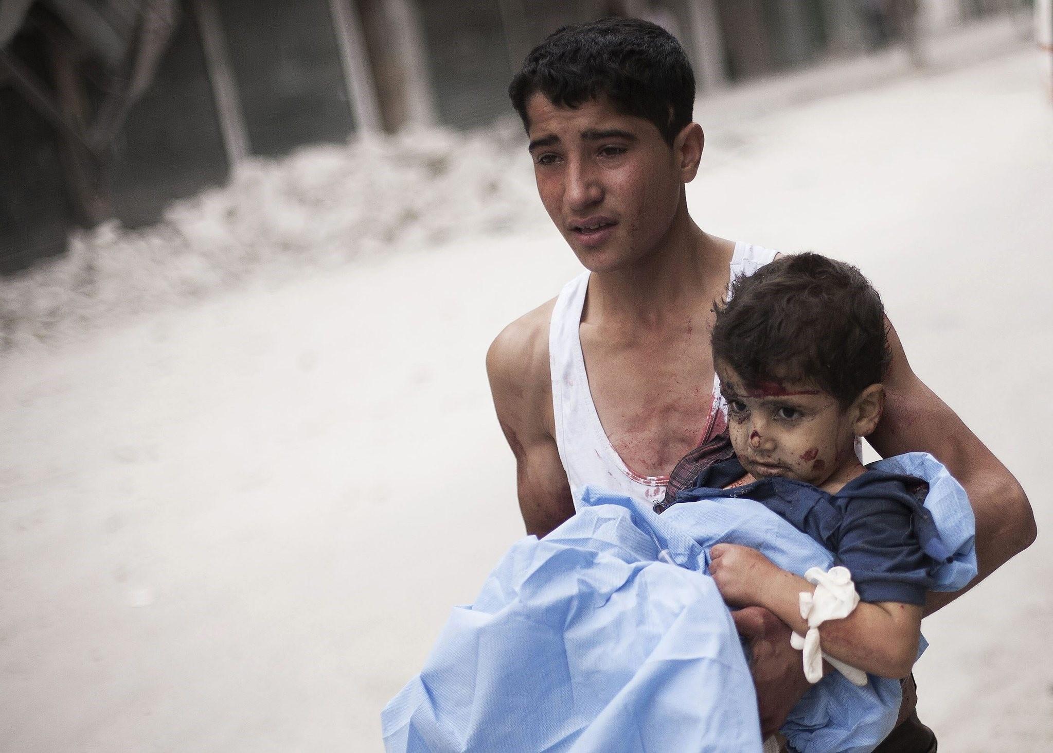 A Syrian youth holds a child wounded by Syrian Army shelling near Dar El Shifa hospital in Aleppo, Syria, Thursday, Oct. 11, 2012. (AP Photo)