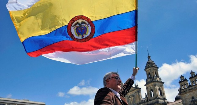 A man holds a Colombian national flag with white stripes during a demo to demand the immediate endorsement of the new peace agreement between the Colombian government and the FARC guerrilla outside the Colombian Congress in Bogota, Nov. 30.