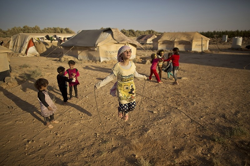 Syrian refugee girl, Zubaida Faisal, 10, skips a rope while she and other children play near their tents at an informal tented settlement near the Syrian border on the outskirts of Mafraq, Jordan, July 19, 2016. (AP Photo)