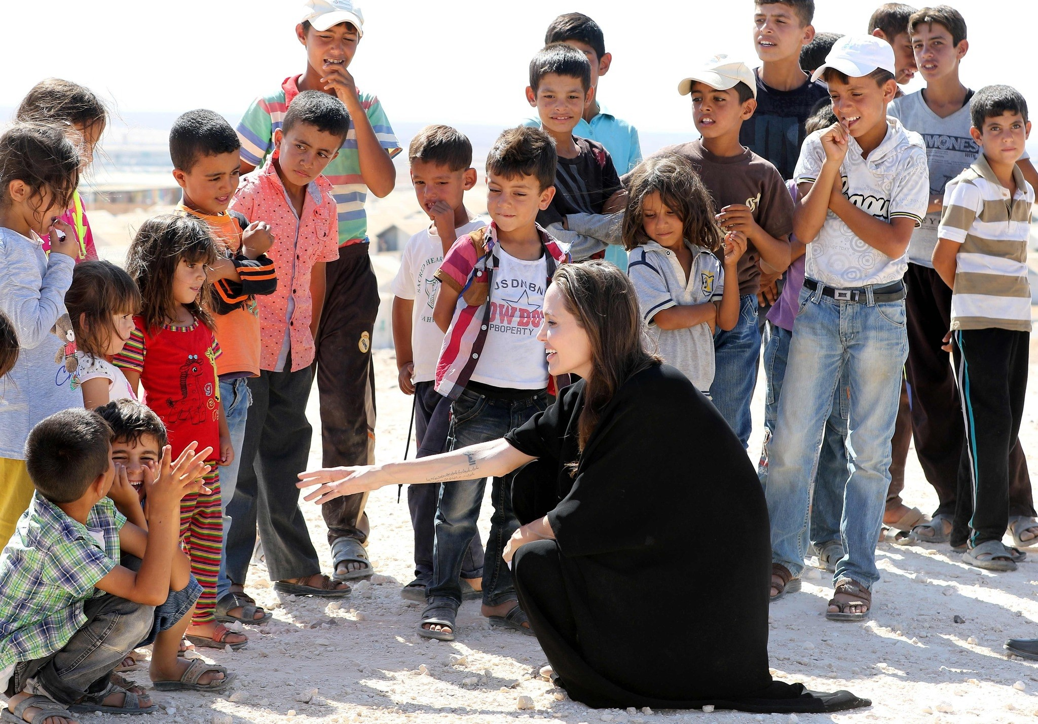 US actress and UNHCR special envoy Angelina Jolie (C) talks to children during a visit to a Syrian refugee camp in Azraq in northern Jordan, on September 9, 2016. (AFP PHOTO)