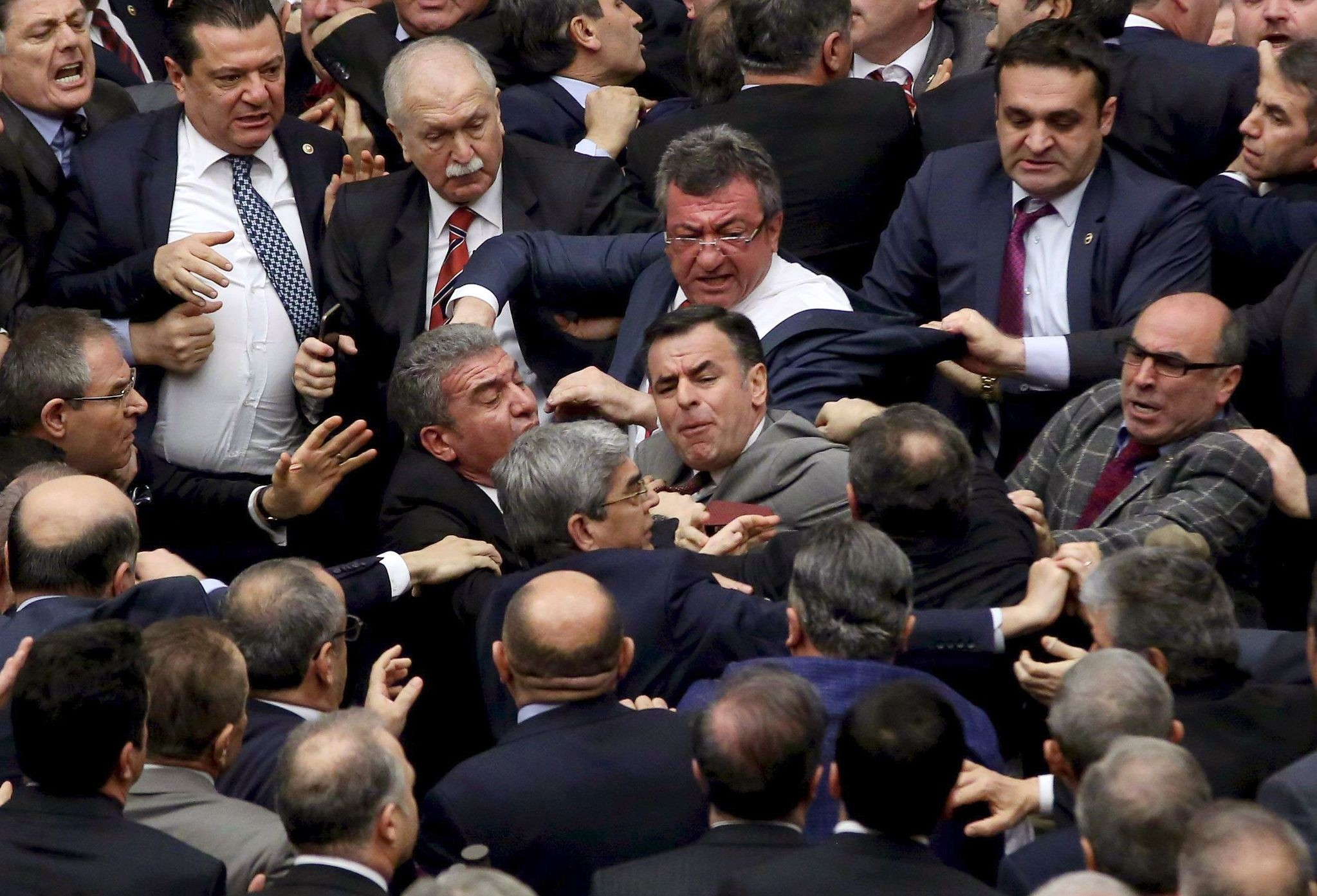 Turkish lawmakers scuffle at the parliament in Ankara during deliberations over a controversial 18-article bill to change the constitution. (AFP Photo)