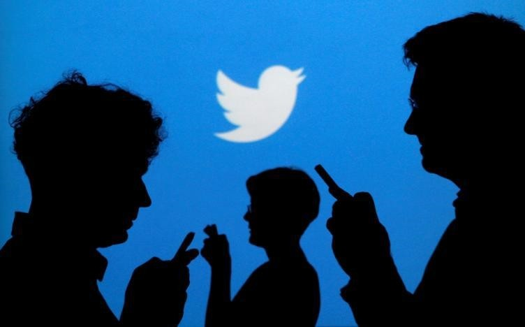 People holding mobile phones are silhouetted against a backdrop projected with the Twitter logo in this illustration picture taken in Warsaw September 27, 2013. (REUTERS Photo)