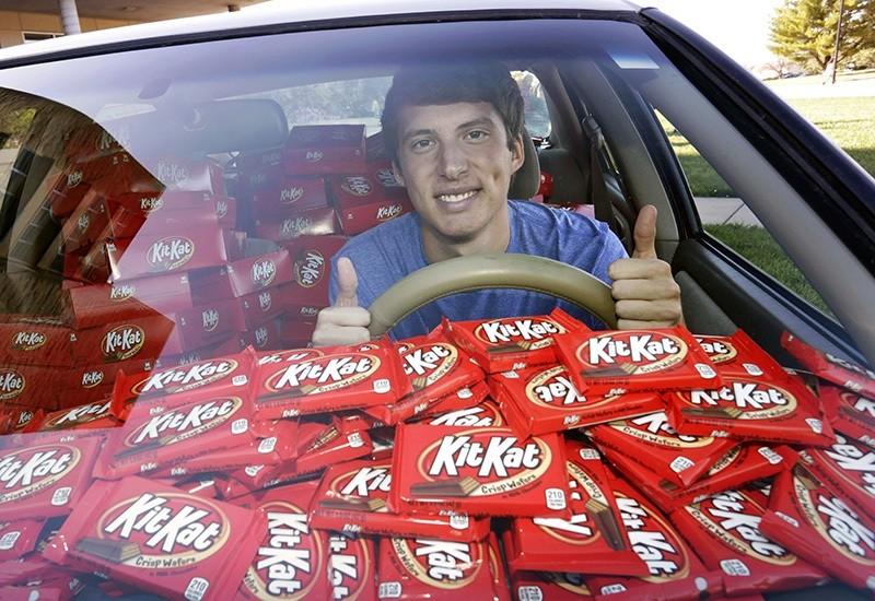 In this Nov. 3, 2016, photo Hunter Jobbins, freshman at Kansas State University, poses in his car filled with nearly 6,500 Kit Kat bars in Manhattan (AP Photo)