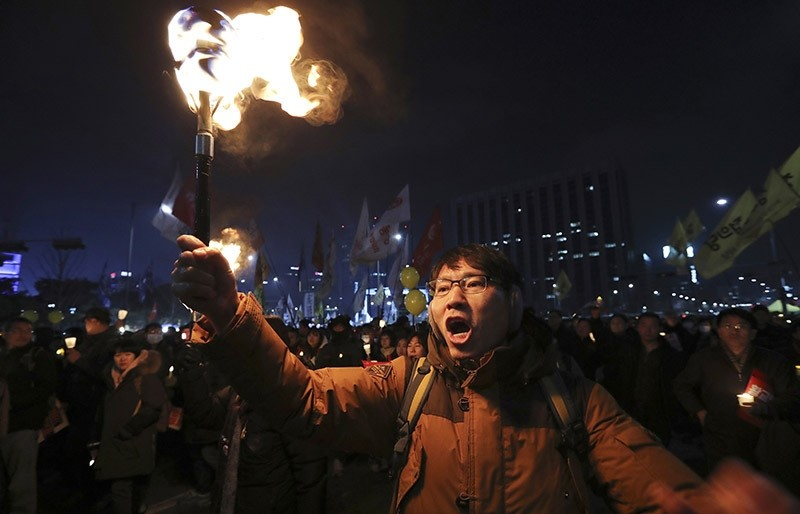 A protester carries a torch with other protesters after a rally against the impeached South Korean President Park Geun-hye in downtown Seoul, South Korea, Saturday, Dec. 17, 2016. (AP Photo)