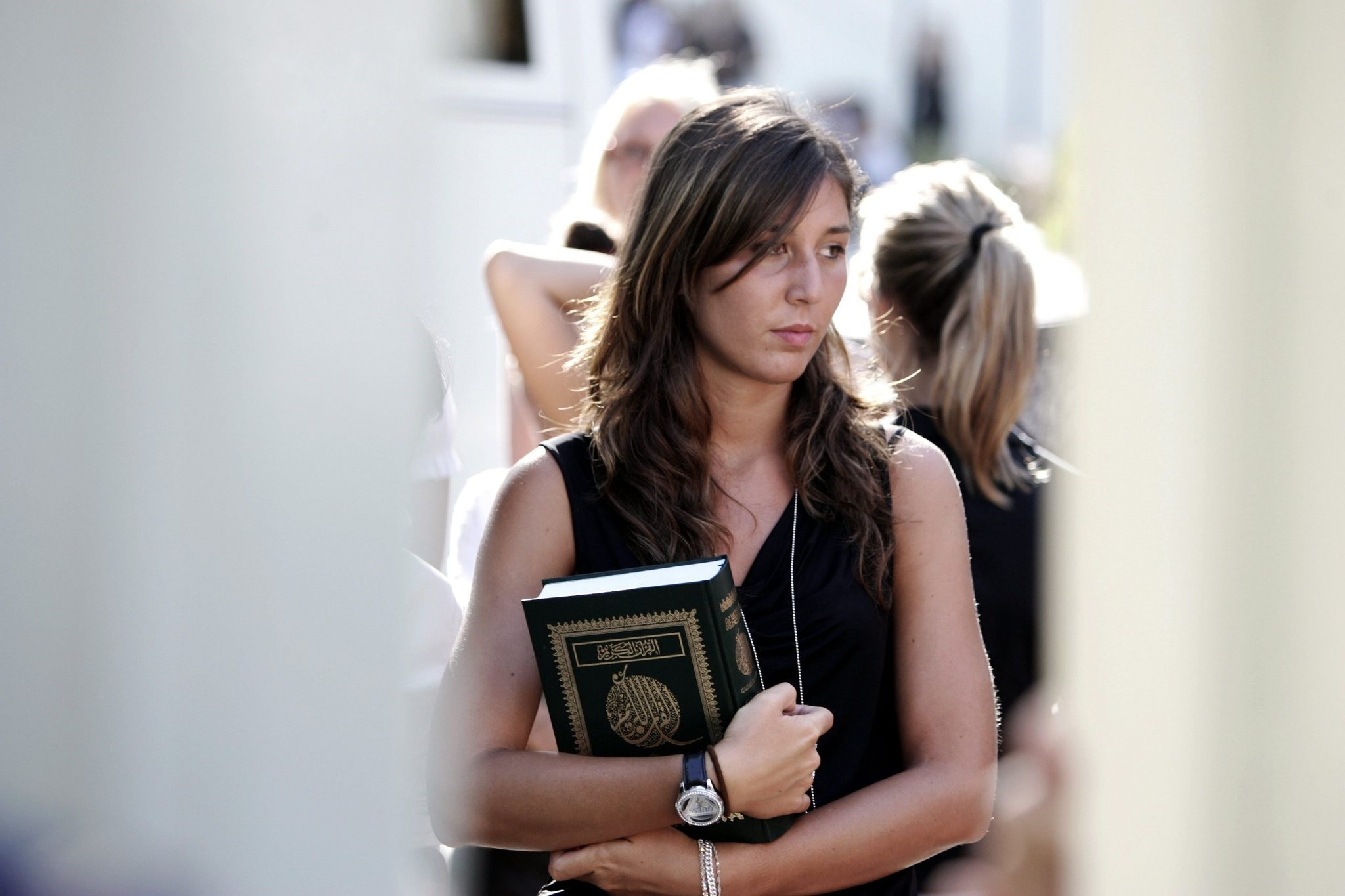 A  woman holds a copy of the Koran after a meeting with Libyan leader Moammar Gadhafi, at the Libyan Academy near the Libyan ambassador's residence in Rome, Sunday, Aug. 29, 2010. (AP Photo)