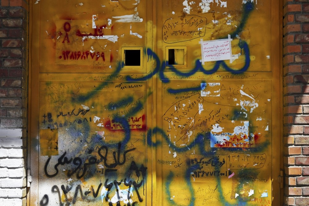 Picture shows handwritten advertisements for kidneys for sale, that include the sellersu2019 phone number and blood type, posted on a door in downtown Tehran.
