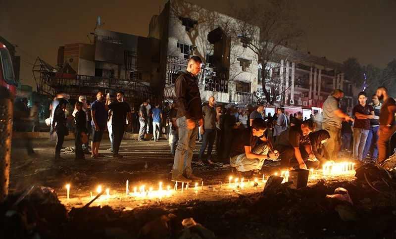 People light candles at the scene of a massive car bomb attack in Karada, a busy shopping district where people were shopping for the upcoming Eid al-Fitr holiday, in the center of Baghdad, Iraq (AP Photo)