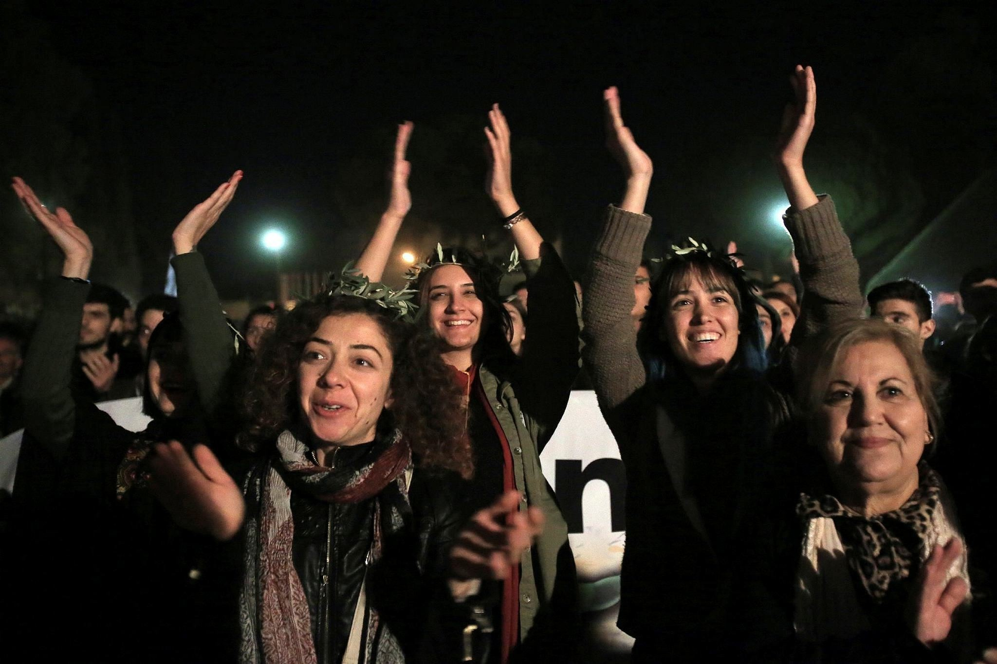 Greek and Turkish Cypriots clap and sing during a peace rally to support the peace talks inside the UN buffer zone ,Green Line, (AP Photo)