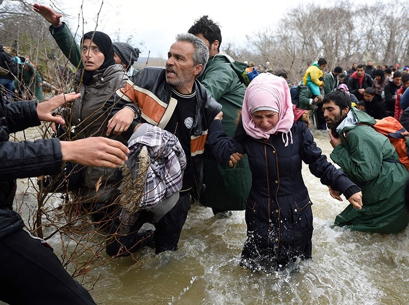 Refugees and migrants try cross a river on their way to Macedonia from a makeshift camp at the Greek-Macedonian border (AFP Photo)