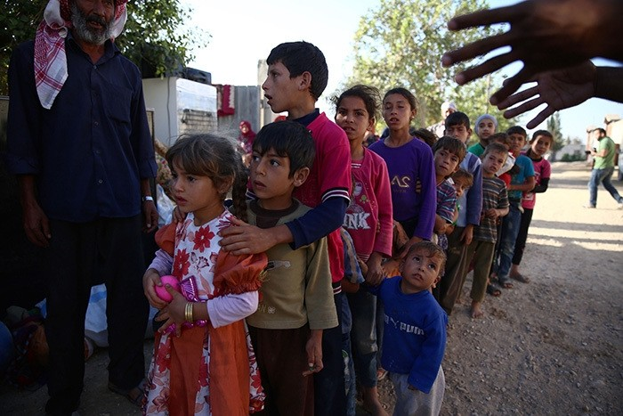 Syrian children, who fled with their families from the village of Hawsh Nasri in Duma, queue to receive aid from an NGO in the village of Shaffuniya in Ghouta, east of the capital Damascus, on August 13, 2016. (AFP Photo)