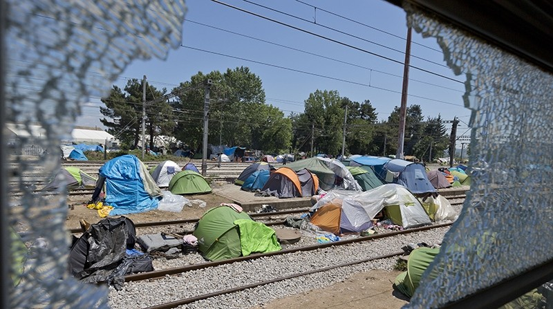 Seen through a broken train window, tents are erected on the railroad linking Greece and Macedonia, at the migrants camp in Idomeni, Greece, Monday, May 23, 2016 (AP Photo)