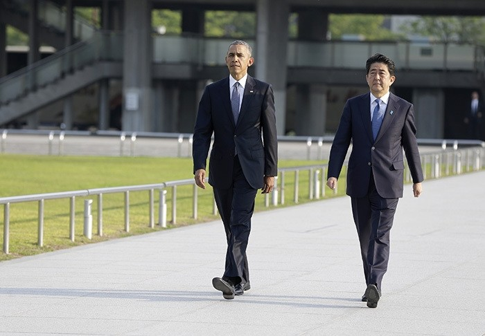 U.S. President Barack Obam, left, walks with Japanese Prime Minister Shinzo Abe for a wreath-laying ceremony at Hiroshima Peace Memorial Park in Hiroshima, western, Japan, Friday, May 27, 2016. (AP Photo)