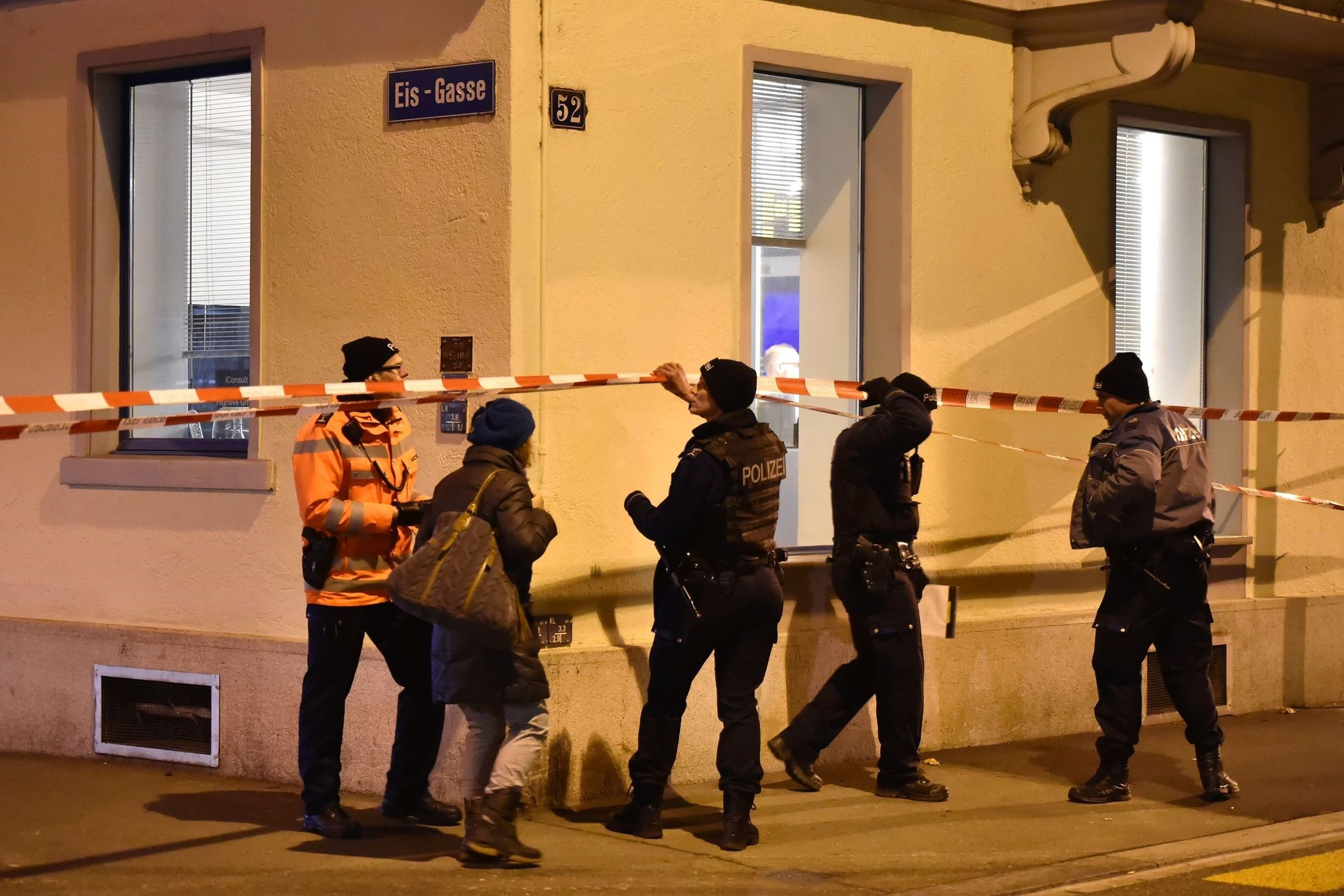 Swiss police walk behind a police cordon outside a Muslim prayer hall at the Eis-Gasse street, central Zurich, on December 19, 2016, after three people were injured by gunfire. (AFP Photo)