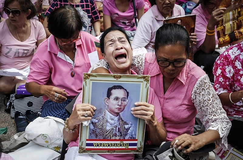 A Thai well-wisher weeps as she is comforted by others during a prayer for Thai King Bhumibol Adulyadej's recovery at the Siriraj Hospital in Bangkok, Thailand (EPA Photo)