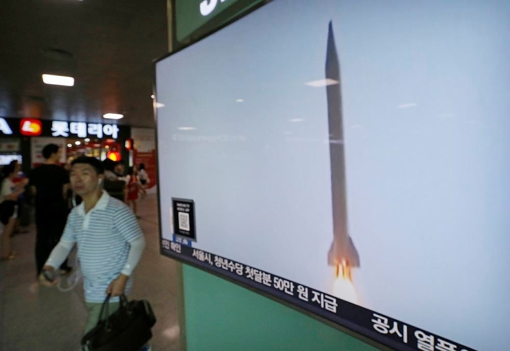 A man passes by a TV news program with file footage of a North Korean rocket launch at the Seoul Railway Station in Seoul, South Korea, Wednesday, Aug. 3, 2016. (AP Photo)
