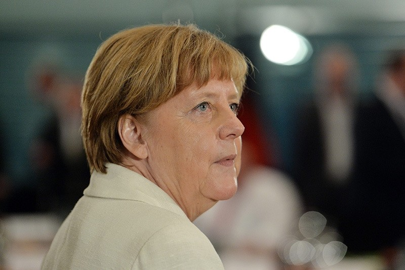 Merkel looks on before the start of a meeting with ministers to discuss about the renewable energy reform (EEG), at the chancellery in Berlin, 31 May 2016. (EPA)