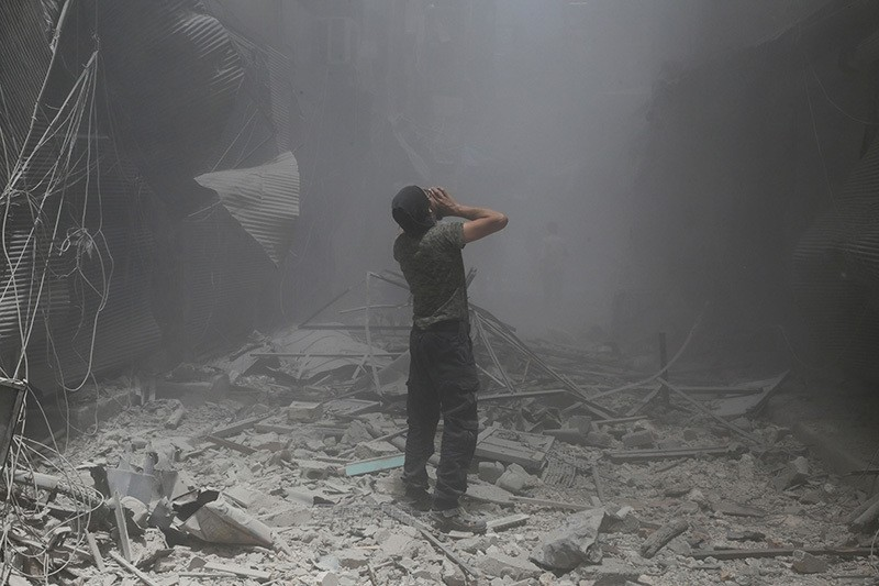 A Syrian man reacts following a reported air strike by Assad forces in the opposition-held neighbourhood of Bustan al-Qasr on June 5, 2016. (AFP)