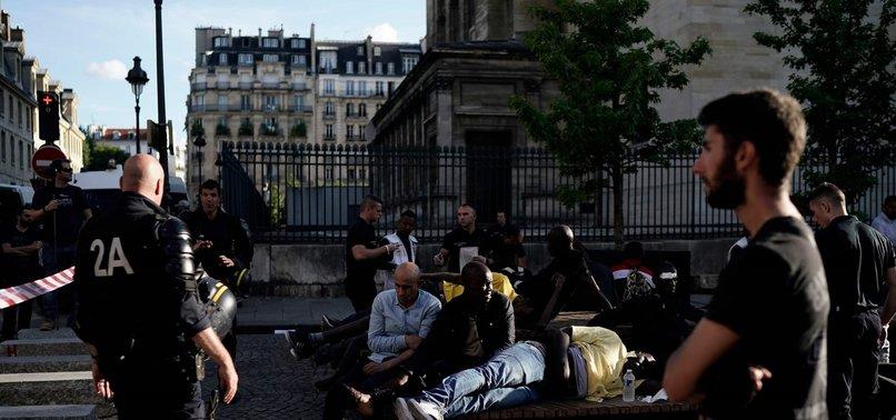 SCORES OF MIGRANTS OCCUPY PARIS LANDMARK
