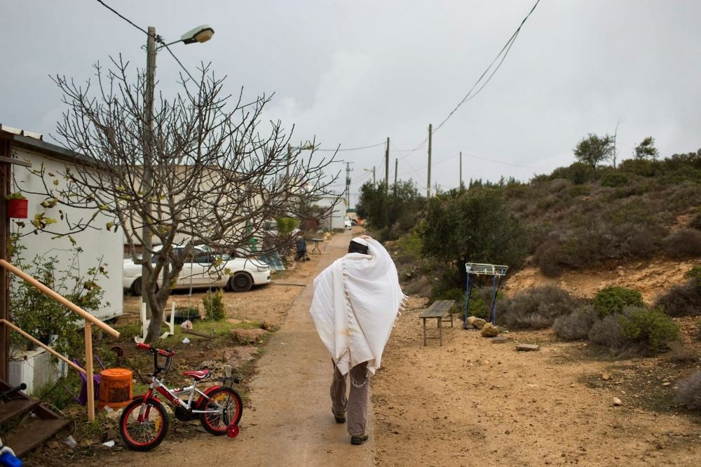 A Jewish settler covered in a prayer shawl walks back to his house after morning prayer in Amona, an unauthorized Israeli outpost in the West Bank, east of the Palestinian town of Ramallah, Dec. 18.