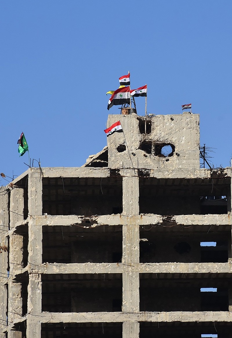 Syrian flags, with YPG flag in the background, flutter on top of a building in Aleppo's Bustan al-Basha neighbourhood on Nov. 28, 2016 during the regime assault to retake the entire northern city from rebel fighters. (AFP Photo)