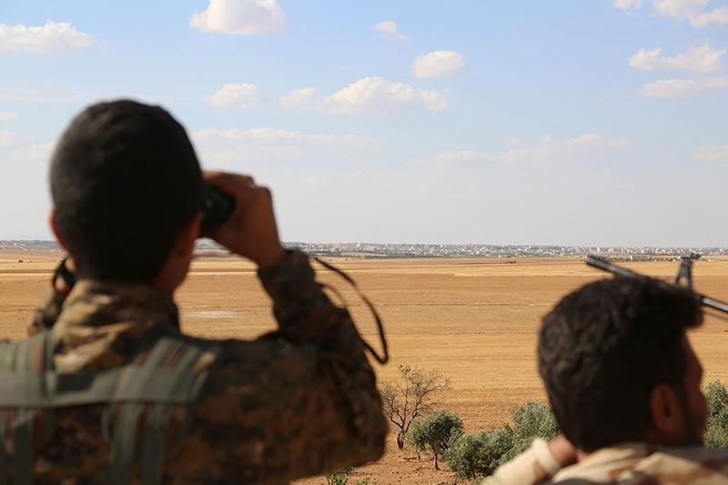 Fighters from the Syrian Democratic Forces (SDF) use binoculars from a view point overlooking the northern Syrian town of Manbij held by Daesh terrorists. (AFP Photo)