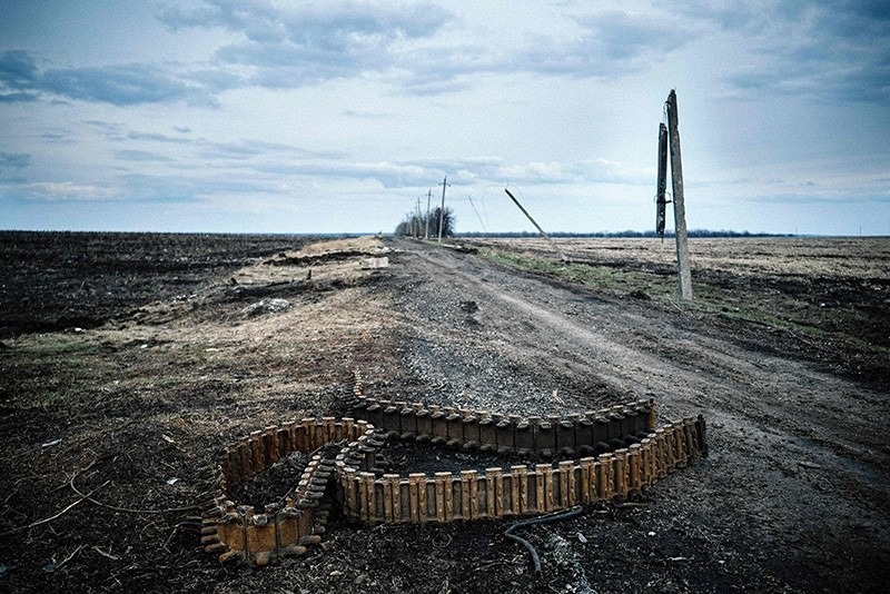 This file photo taken on April 06, 2015 shows a chain of destroyed Armour Personnel Carrier on the ground in a field near the village of Nikishino, eastern Ukraine. (AFP Photo)