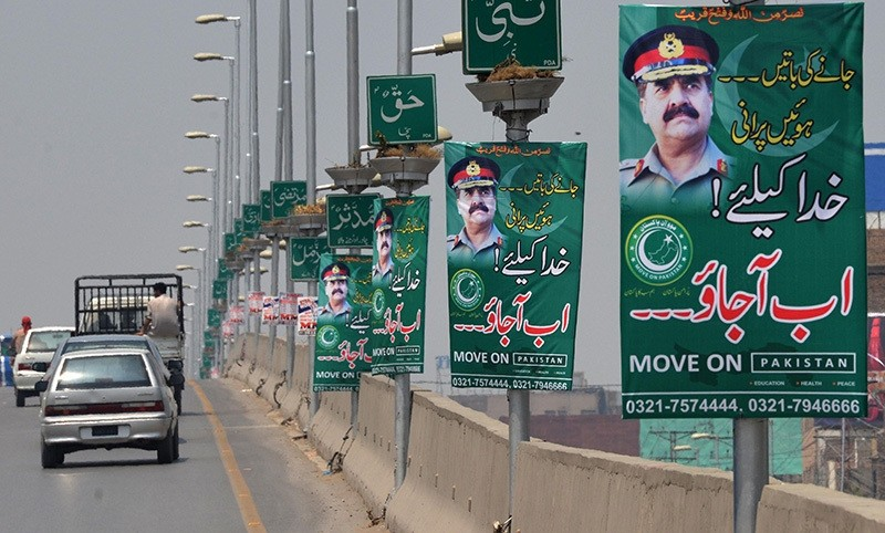 Pakistani commuters drive past posters of army chief General Raheel Sharif in Peshawar on July 12, 2016. (AFP Photo)