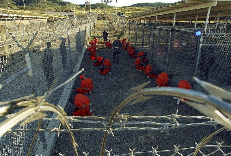 In this file photo, detainees in orange jumpsuits sit in a holding area under the watchful eyes of military police during in-processing to the temporary detention facility at Camp X-Ray of Naval Base Guantanamo Bay. (Reuters Photo)