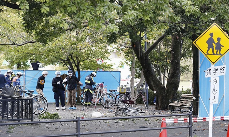 Police officers investigate near a damaged wooden bench, right, following an explosion at a park in Utsunomiya, north of Tokyo, Sunday, Oct. 23, 2016. (AP Photo)