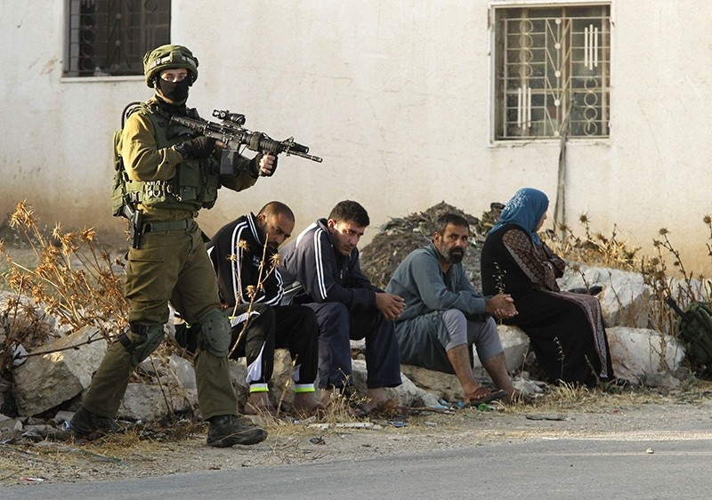 An Israeli soldier keeps watch as Palestinians sit nearby after the army entered the village of Yatta in the occupied West Bank on June 9,2016 (AFP)