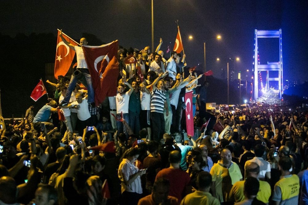 A large group of people denouncing the coup attempt on an abandoned tank, holding Turkish flags on the July 15 Martyrs' Bridge (Bosporus Bridge).