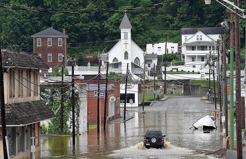 A vehicle makes a wake along the flooded Lower Oakford Ave. Friday, June 24, 2016, in Richwood, W.Va.  Archive Photo