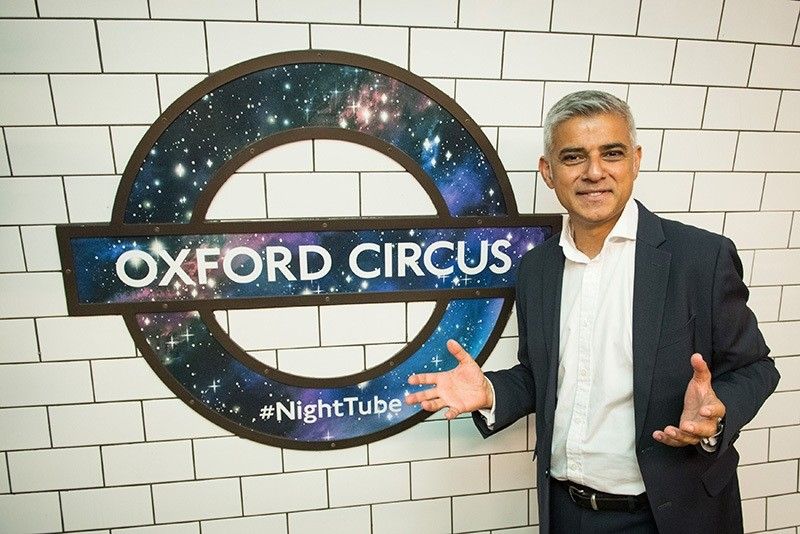 Mayor of London Sadiq Khan poses in front of a new Night Tube logo at Oxford Circus underground station, in London Thursday Aug. 18, 2016. (AP Photo)