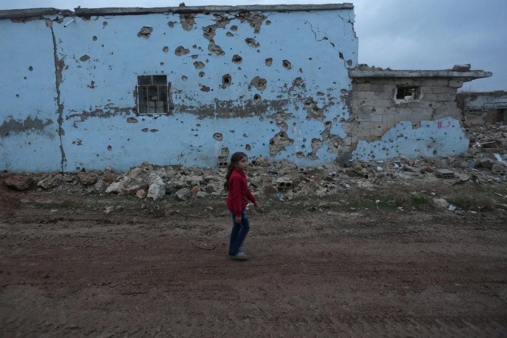 A girl walks near a damaged house in al-Rai town, northern Aleppo province, Syria on Dec. 27, 2016.