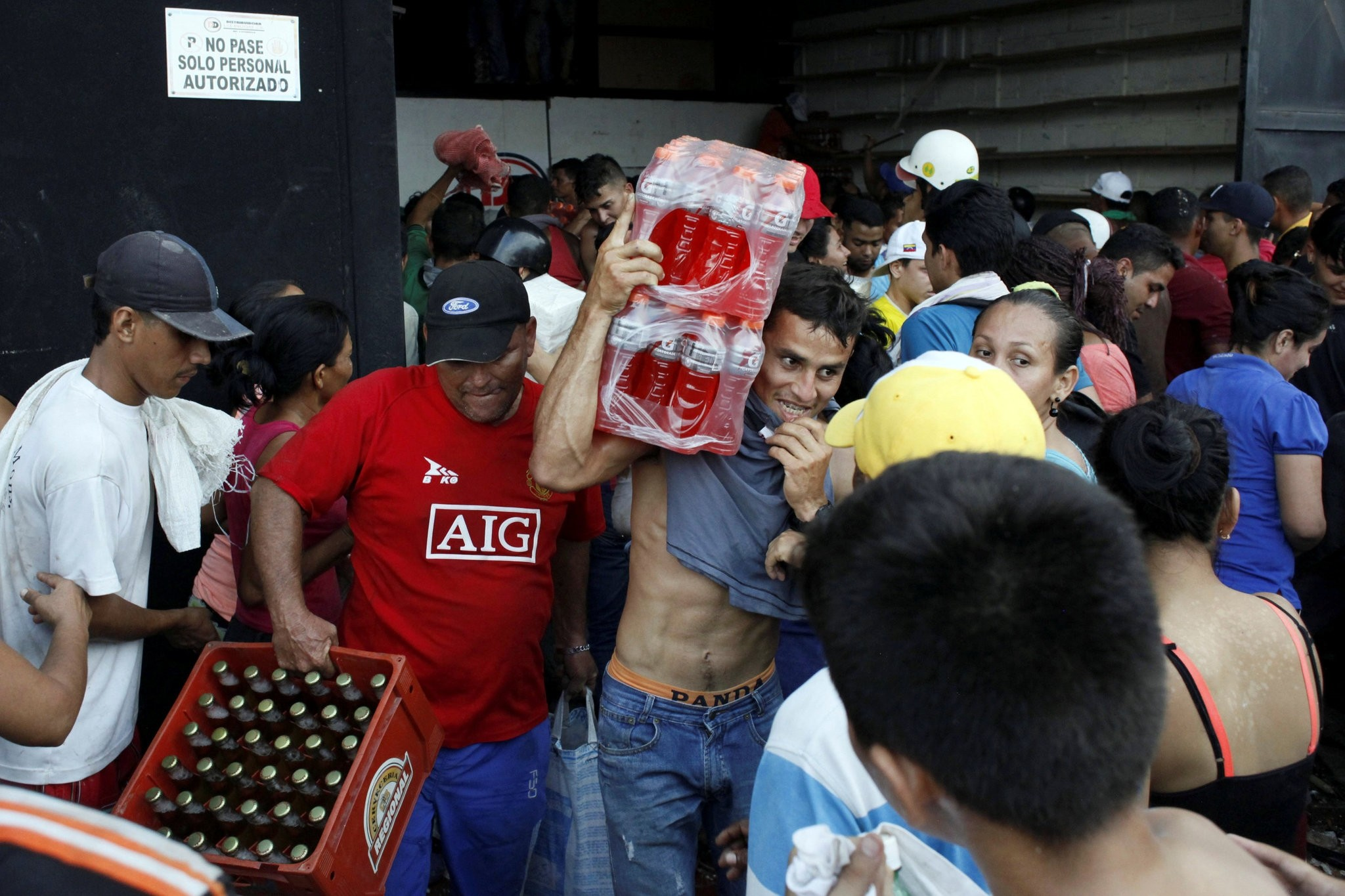 People hold up 100-Bolivar notes during a protest over the lack of cash as the new bank notes have not yet appeared, at the u201cTroncal 5u201d road in San Cristobal in Venezuelau2019s Tachira state.