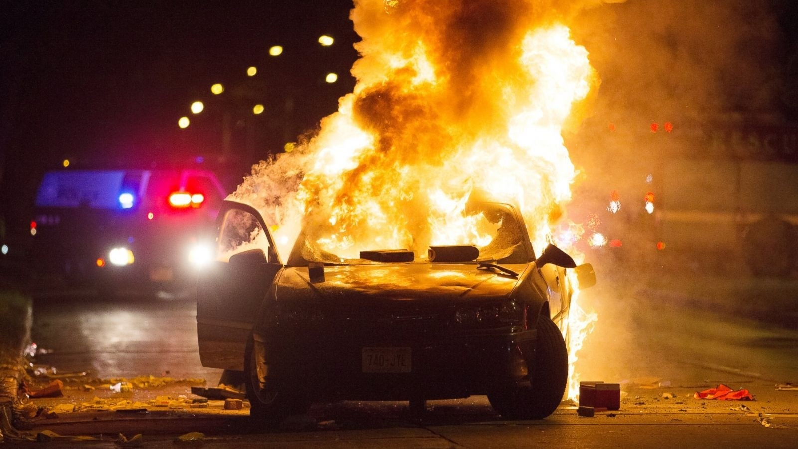 A car burns as a crowd of more than 100 people gathers following the fatal shooting of a man in Milwaukee, Saturday, Aug. 13, 2016.  AP Photo