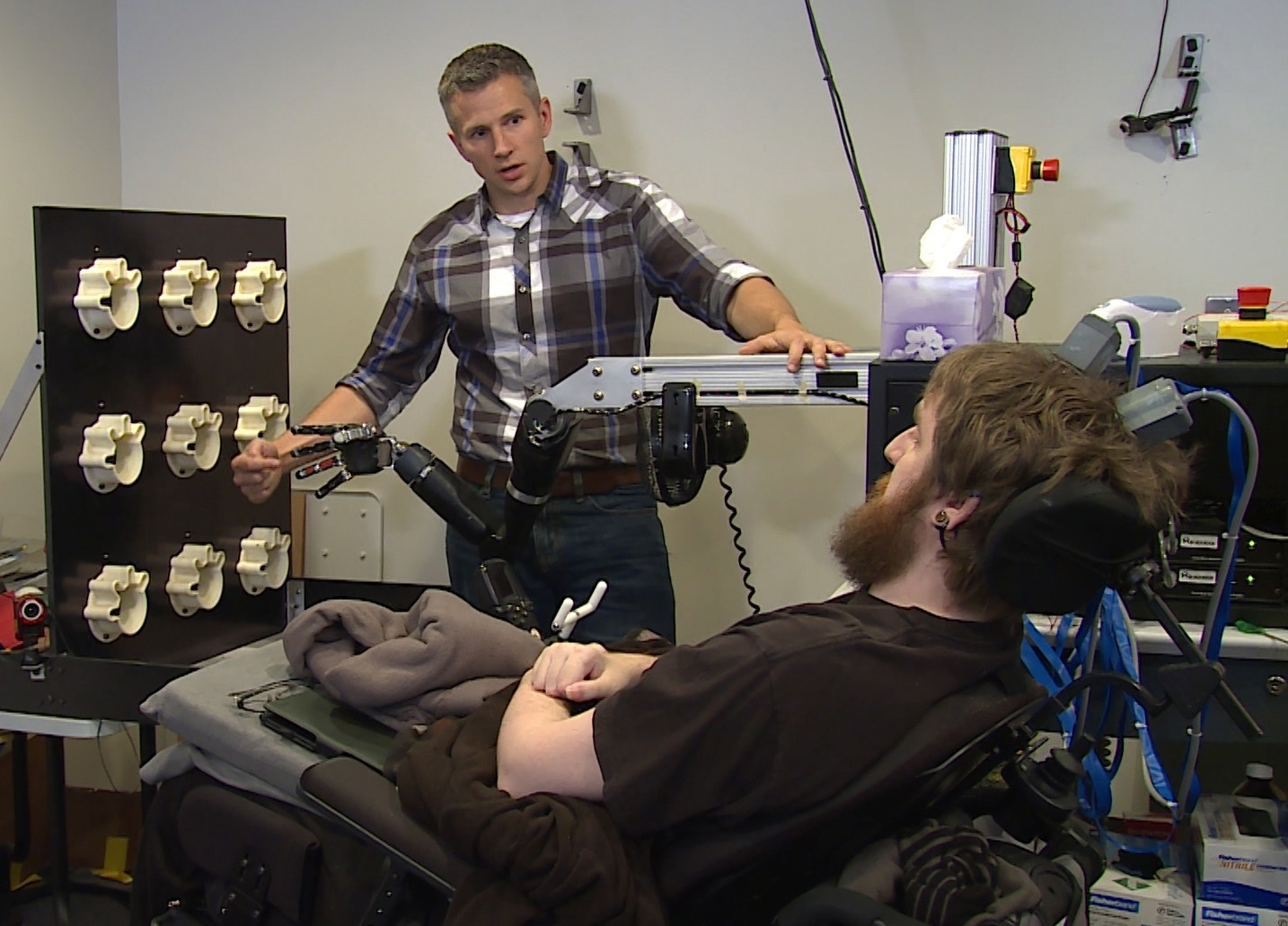This image from video, provided by UPMC/Pitt Health Sciences, taken Oct. 26, 2015, shows University of Pittsburgh researcher Robert Gaunt preparing Nathan Copeland. (AP Photo)