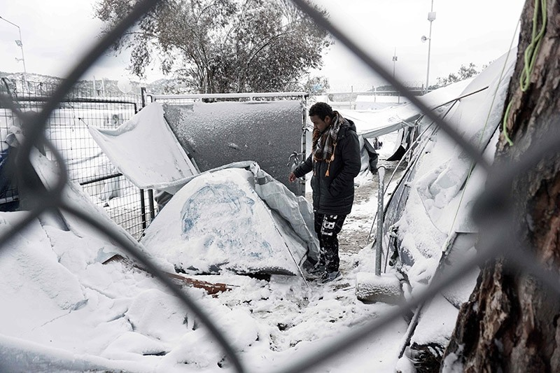 A migrant stands next to a snow-covered tent at the Moria hotspot on the island of Lesbos , following heavy snowfalls on January 7, 2017. (AFP Photo)