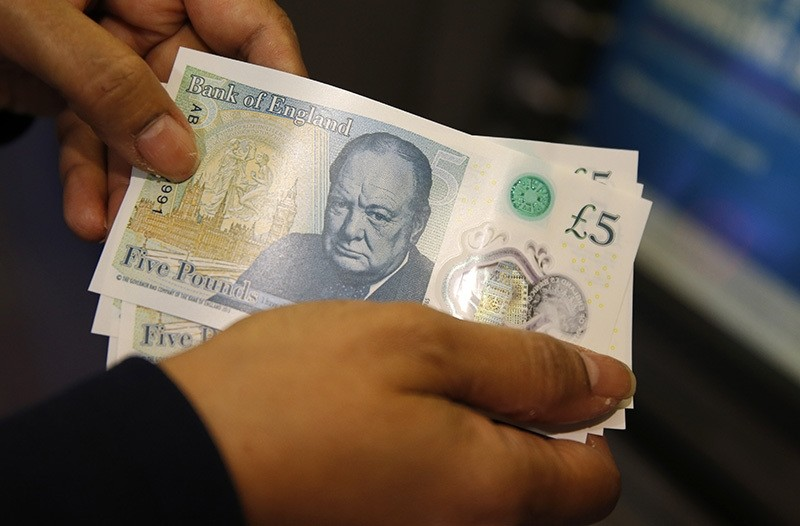 Amanda a member of staff at a branch of Halifax bank, in London, displays the new British 5 pound sterling notes, made from polymer, which were launched Tuesday, Sept.13, 2016. (AP Photo)