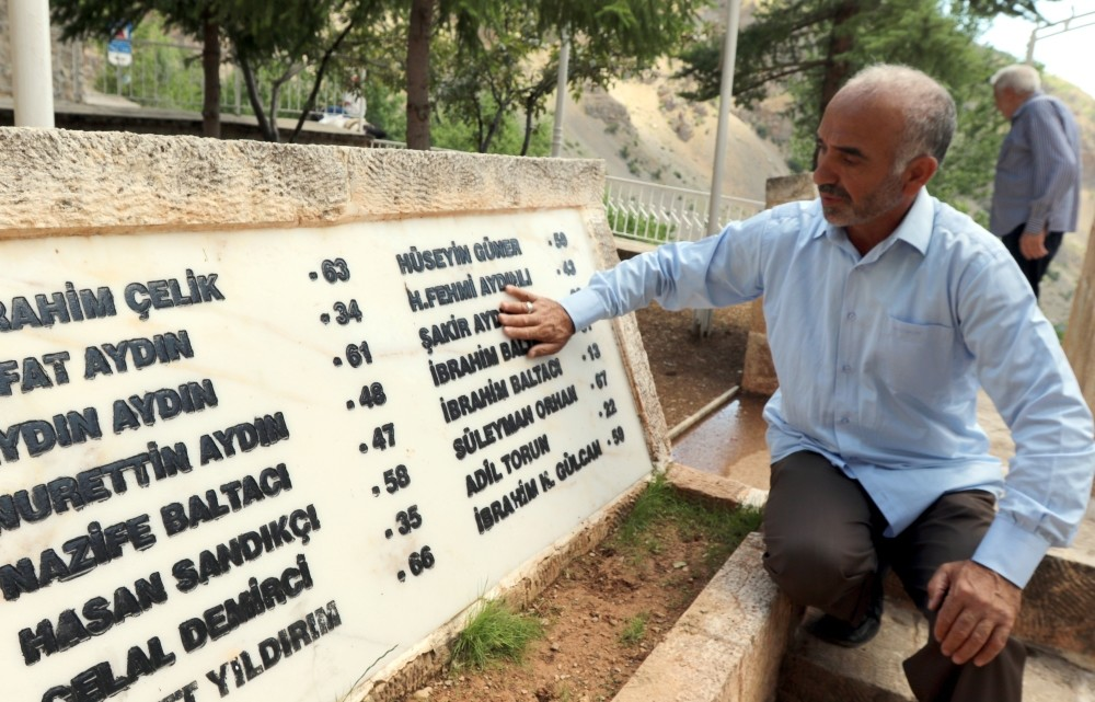 Locals visit a monument with the names of the victims.
