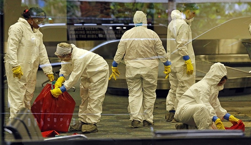 A hazmat crew cleans up baggage claim Terminal Two on Saturday, Jan. 7, 2017 at Fort Lauderdale-Hollywood International Airport Terminal the day after multiple people were shot on Friday. (AP Photo)