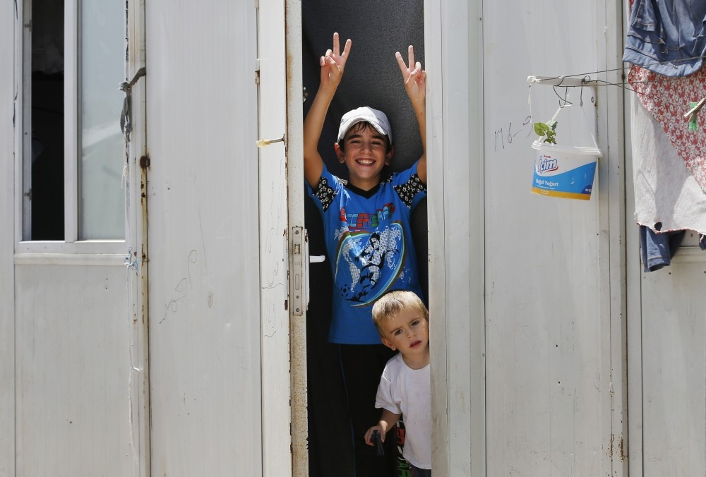 A Syrian boy showing the v sign from a container at the u00d6ncu00fcpu0131nar camp for Syrian refugees in the Kilis province of Turkey.