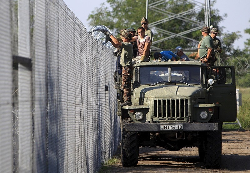 Hungarian soldiers adjust the razor wire on a fence near the town of Asotthalom, Hungary. Aug. 2015. (Reuters Photo)