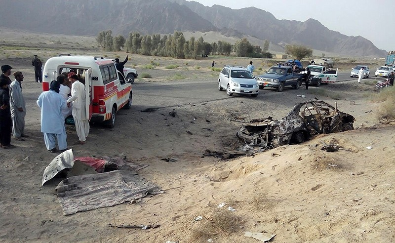 This Saturday, May 21, 2016 file photo taken by freelance photographer Abdul Malik, purports to show volunteers standing near the wreckage of the destroyed vehicle, in which Mullah Akhtar Mansour was allegedly traveling (AP Photo)