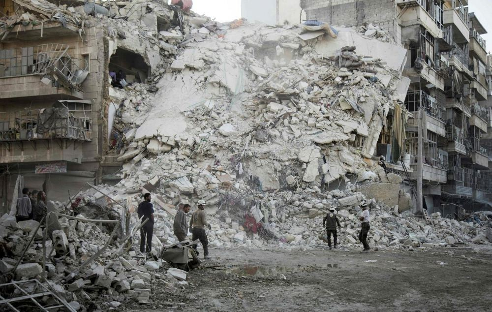 Members of the Syrian Civil Defense, known as the White Helmets, search for victims amid the rubble of a destroyed building following reported air strikes in the opposition-held Qatarji neighborhood of the northern city of Aleppo, on Oct. 17.